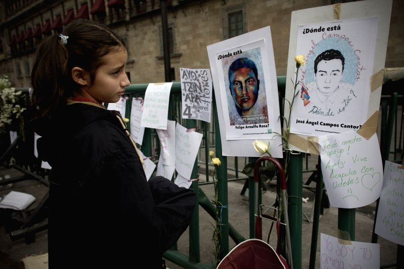 A girl looks at the letters and photographs placed during a demonstration held outside National Palace for the missing students of the Normal Rural School of ...