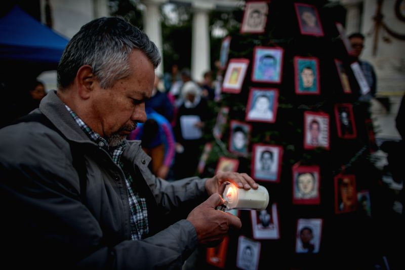 """A man lights a candle during the installation of the tree """"Truth, Justice and Peace for Ayotzinapa"""", which is decorated with the portraits of missing ."""