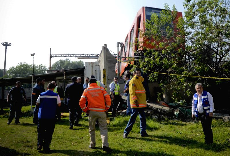 Employees work at the site where a train of Metro Public Transport System knocked down a wall and hung suspended in the final zone of the Rosario Workshop, in ..