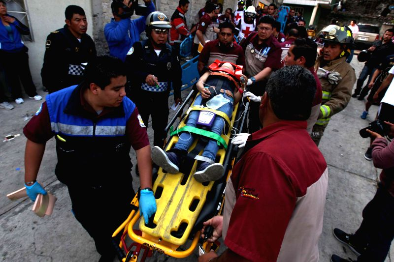 Rescuers carry an injured person at a bus accident site in Mexico City, capital of Mexico, on Dec. 28, 2014. Xinhua/Str/IANS)