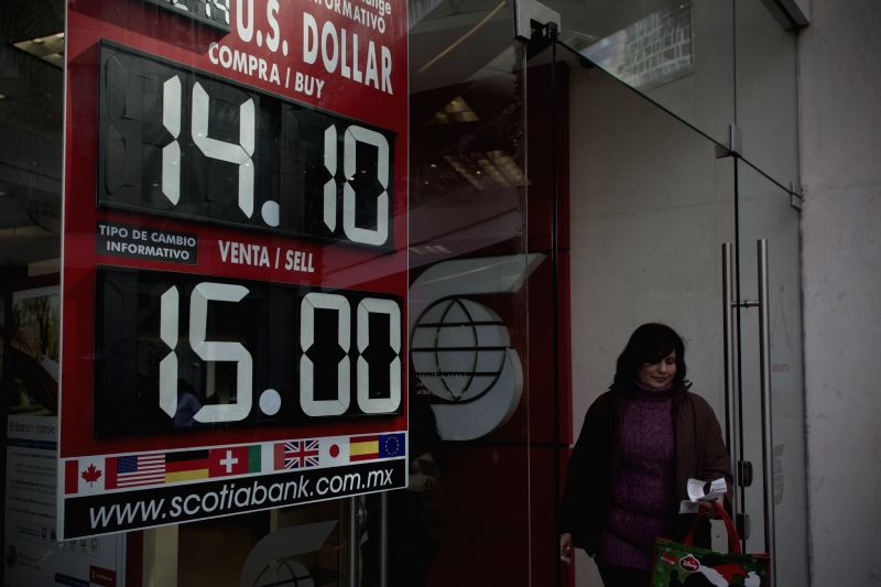 A person walks in front of a bank branch, where the exchange rate of Mexican peso against U.S. Dollar is shown, in Mexico City, capital of Mexico, on Dec. 29, ..