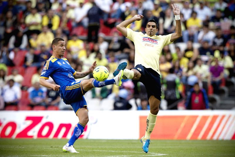 America's Cristian Pellerano (R) vies with Tigres' Jesus Duenas during a match of the Closing Tournament 2015 of MX League in the Azteca Stadium, in Mexico City,
