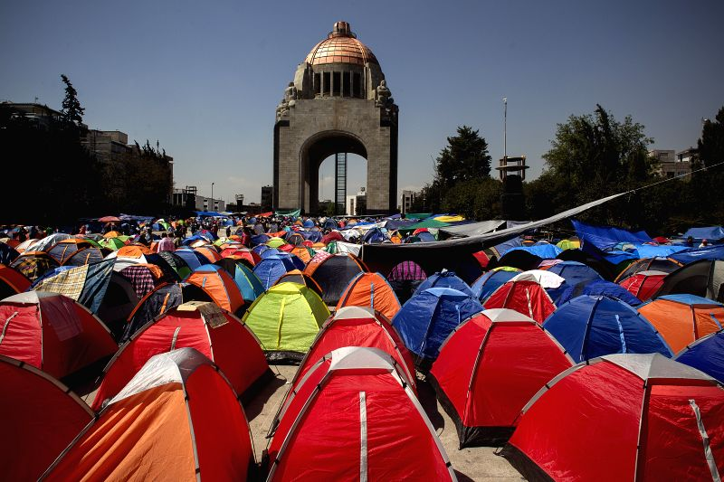 Teachers of the National Coordinator of Education Workers of Oaxaca state take part in an encampment during a protest in the esplanade of the Monument to the ...