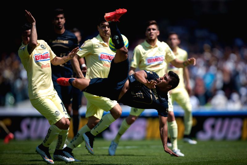 UNAM's Pumas Javier Cortes (front R) vies with America's Osmar Mares (front L) during the match of the 2015 Closing Tournament of MX League in the Olympic ...