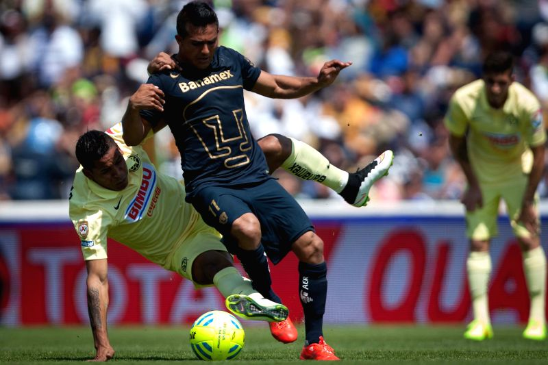 UNAM's Pumas Javier Cortes (R) vies with America's Michael Arroyo during the match of the 2015 Closing Tournament of MX League in the Olympic University Stadium ...