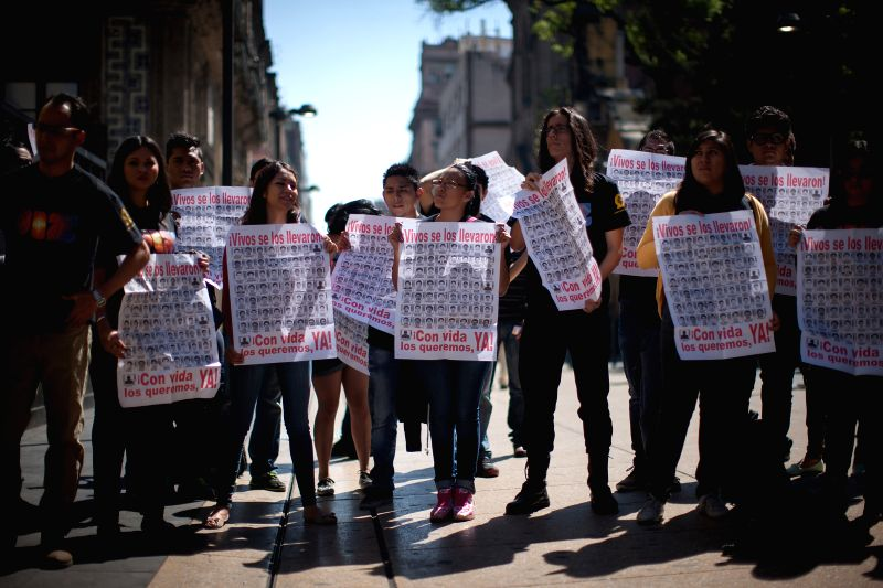 Residentes shout slogans during a peaceful demonstration held as part of the commemoration of the five months of the disappearance of 43 students from the ...