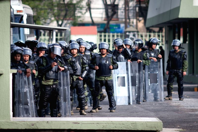 Riot military police watch the barracks of the Presidential Guard Corps during a march to demand justice in the case of 43 missing students of the Normal Rural .
