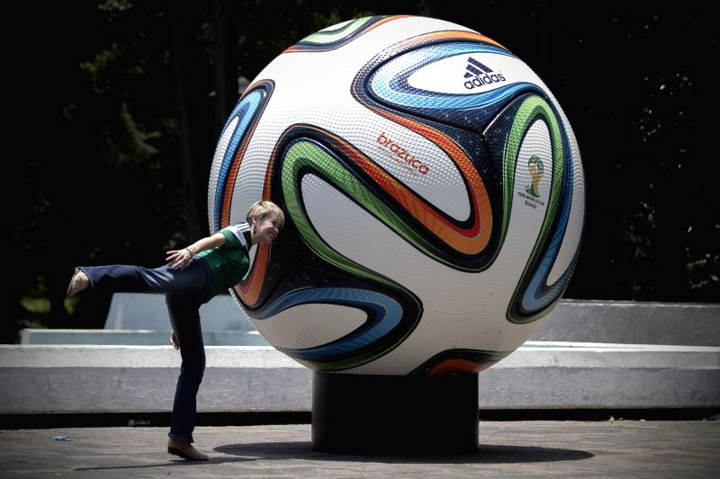 A resident poses in front of a football model, which is part of an exposition of giant replicas of official footballs used by FIFA Wolrd Cup tournaments, in the