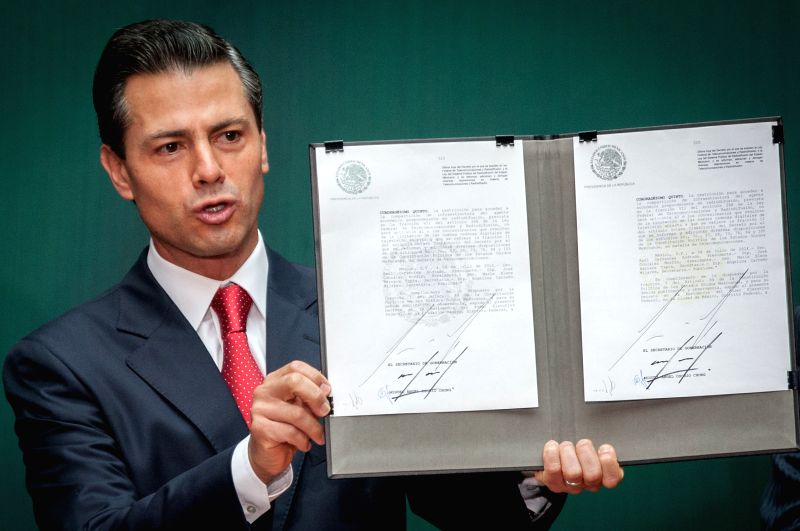 Mexican President Enrique Pena Nieto shows the promulgation's document of federal telecommunications law during a ceremony at the National Palace, in Mexico ...