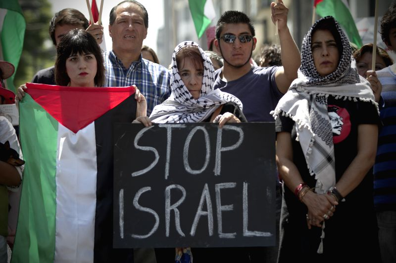 A woman holds a placard during a protest against Israeli's airstrikes on Gaza and in solidarity with the Palestinians, in Mexico City, capital of Mexico, on ...