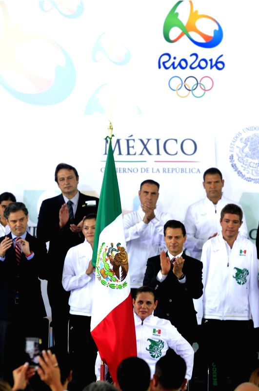 MEXICO CITY, July 22, 2016 - Mexican President Enrique Pena Nieto (3rd R) applauds while swimmer Nely Miranda (C Front) holds the national flag during the flag-bearing ceremony of the Mexican Olympic ...