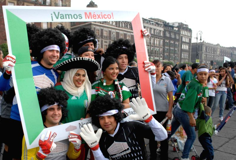 Mexican fans celebrate after the Group A of 2014 Brazil FIFA World Cup match between Croatia and Mexico, at the Monument to the Independence, in Mexico City, ...