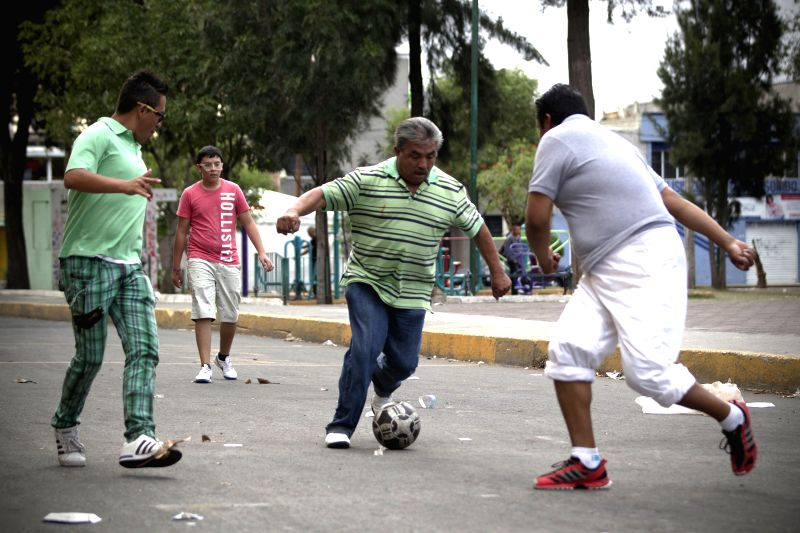 Photo: Image taken on May 11, 2014 of local residents play soccer on the street in Mexico City, capital of Mexico. This informal variant of soccer does not use ..