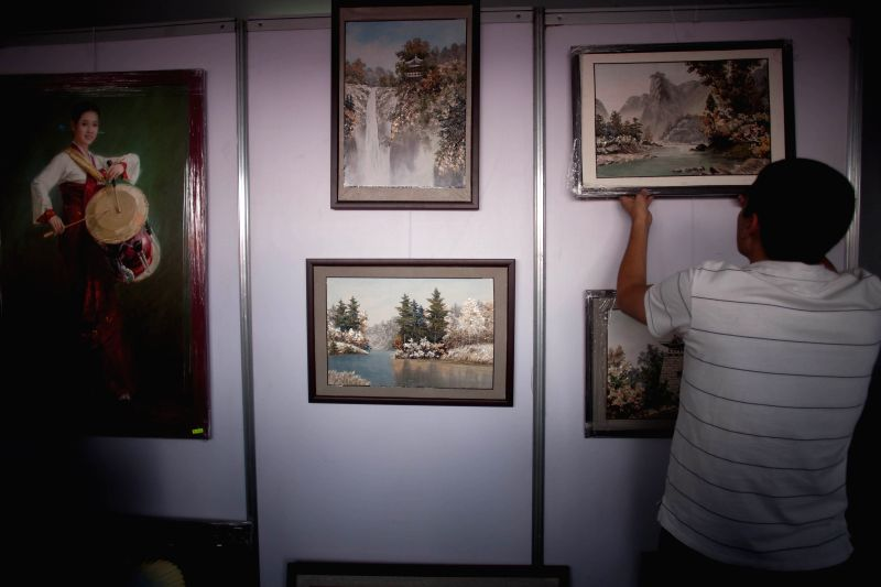 """A man places paintings during the """"Feria de Culturas Amigas 2014"""", at the Constitution Square in Mexico City, capital of Mexico, on May 17, 2014."""