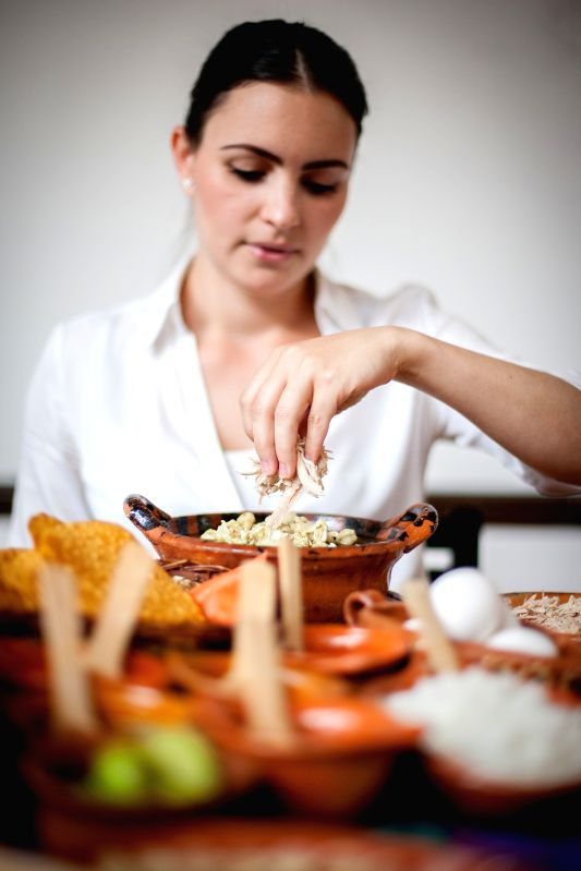 """A woman prepares a portion of """"pozole"""" (corn soup) in the Pozoleria Tixtla Restaurant, in Mexico City, capital of Mexico, on May 7, 2014. The pozole is ."""