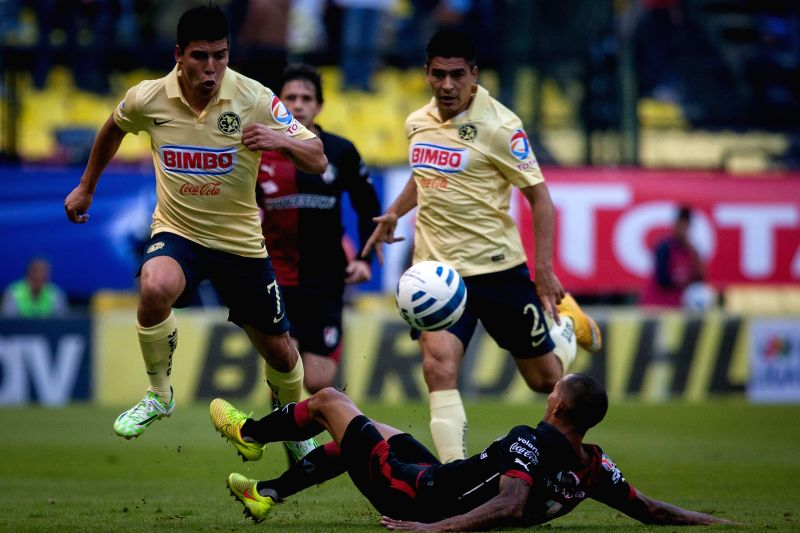 Mexico City (Mexico ): America's Luis Mendoza (L) vies for the ball with Edgar Castillo (Bottom) of Atlas during the match of the Day 17 of the 2014 Opening Tournament of MX League in Azteca Stadium .