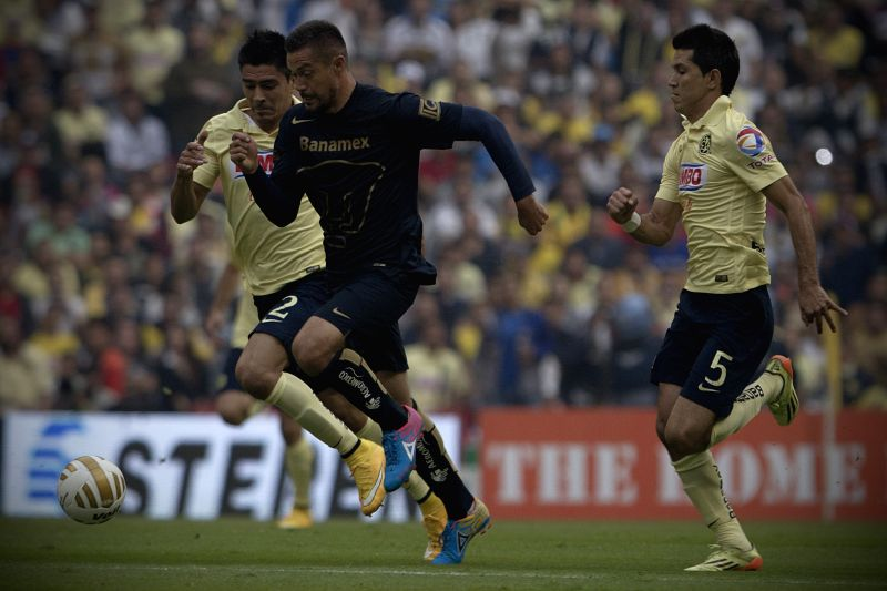 Mexico City (Mexico): Paolo Goltz (L) and Jesus Molina (R) of America vies with Dante Lopez (C) of UNAM's Pumas during the quarterfinal match of Opening Tournament of the MX League at Aztec Stadium, .