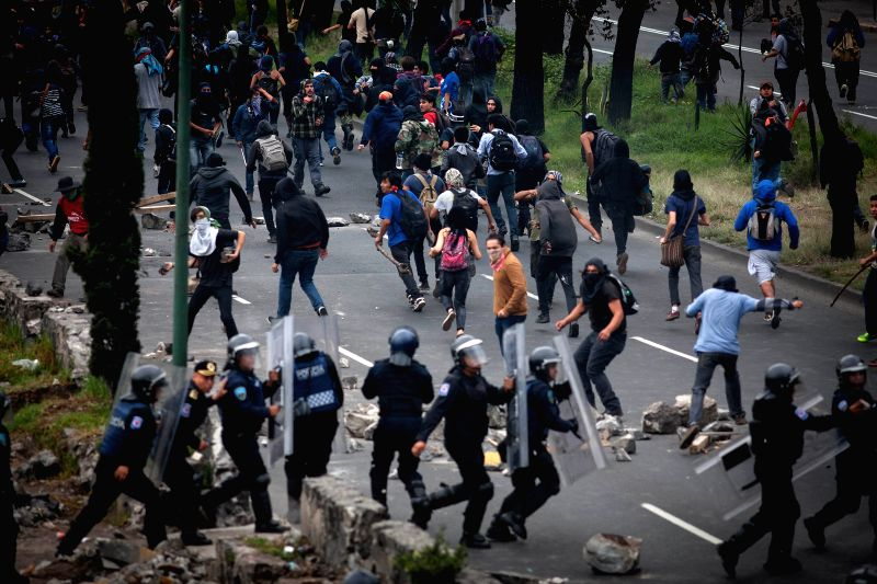Mexico City (Mexico): People with the face covered clash with riot police near Mexico City's International Airport, in Mexico City, capital of Mexico, on Nov. 20, 2014. As part of the commemoration ..
