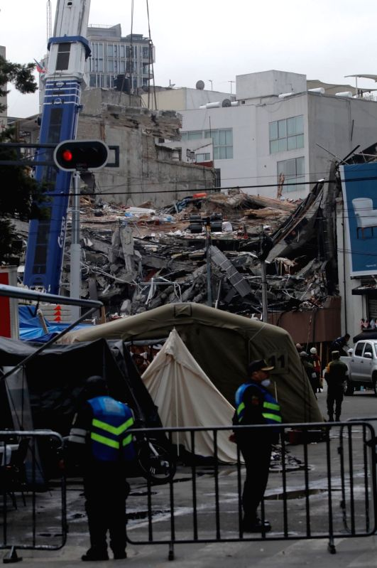 MEXICO CITY, Sept. 30, 2017 - Police stand guard in front of a building that collapsed after the earthquake of Sept. 19, in Mexico City, capital of Mexico, on Sept. 29, 2017. The death toll of the ...