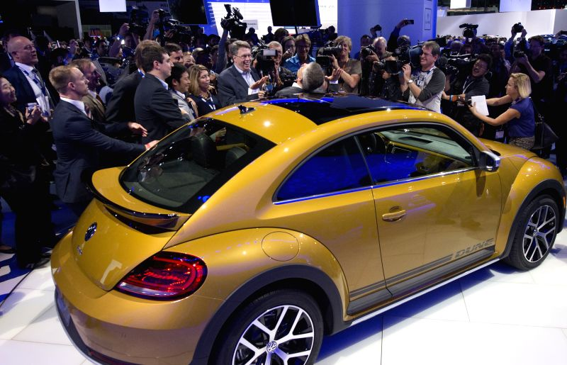 Michael Horn, president and CEO of Volkswagen Group of America, leans on the car as he met with the media at the Los Angeles Auto Show in Los Angeles, the ...