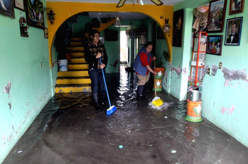 Residents clean their home after a flood in Morelia, Michoacan, Mexico, on March 16, 2015. According to the local press, the frequent rains in Morelia have ...