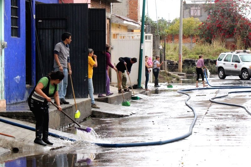 Residents clean a street after a flood in Morelia, Michoacan, Mexico, on March 16, 2015. According to the local press, the frequent rains in Morelia have caused ...
