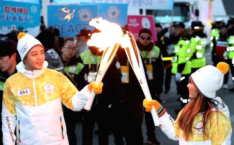 Miki Ando, ancienne patineuse artistique japonaise et ambassadrice de bonne volonté de la province du Gangwon, transmet la flamme des Jeux olympiques d'hiver de PyeongChang à l'acteur ...