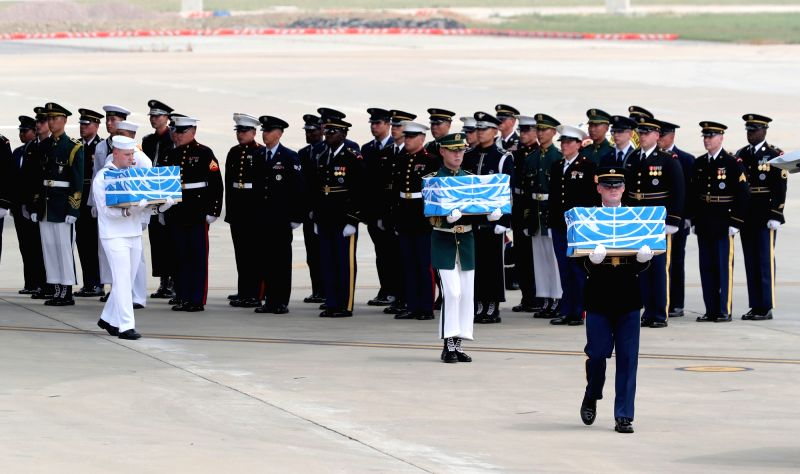 Military personnel carry boxes containing the remains of U.S. soldiers, killed in the 1950-53 Korean War, out of the C-17 Globemaster, a U.S. Air Force transport aircraft, at Osan Air ...