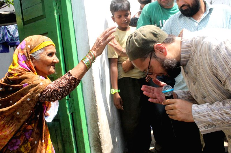MIM chief Asaduddin Owaisi seeks blessings from an elderly lady during an election campaign in Hyderabad on April 11, 2014.