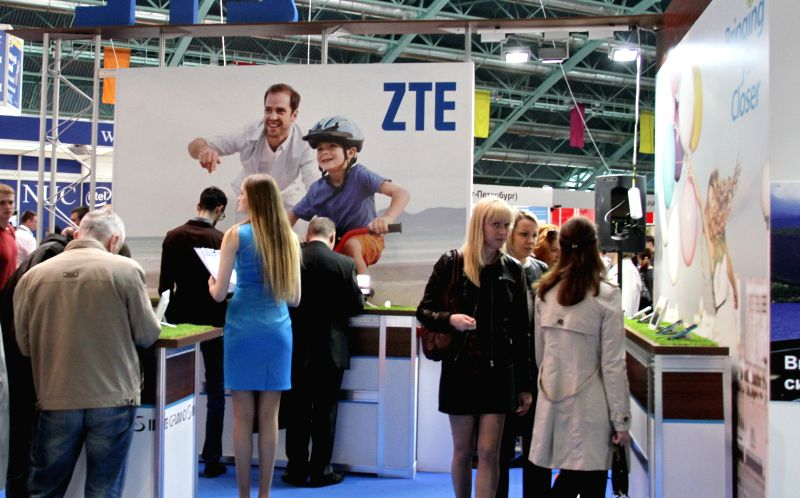 People stand at the booth of ZTE Corporation, a leading telecom equipment manufacturer in China, during an international information technology exhibition in Minsk, .