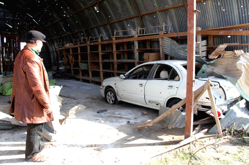 Photo taken on Jan.19, 2015 shows a man standing in a damage garage in Misrata, Libya. Fighters affiliated to the pro-secular and Islamist forces warred against ...