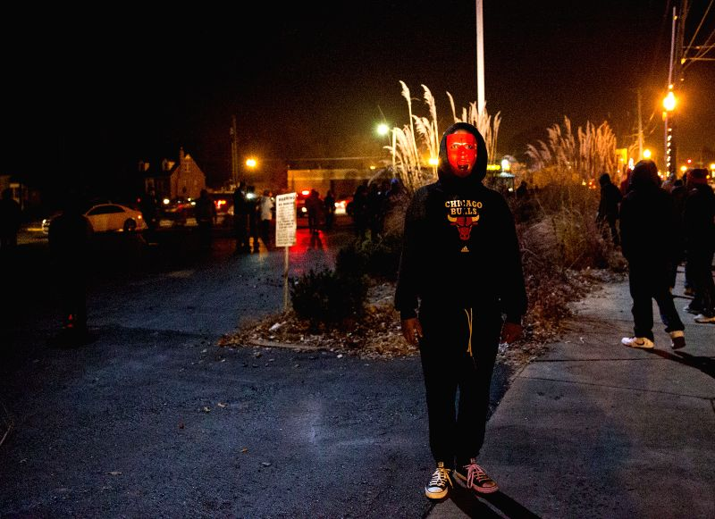 Missouri (United States): A demonstrator attends a protest in Ferguson, Missouri, the United States of America, on Nov, 25, 2014. Violence erupted Monday night in Ferguson after the announcement that