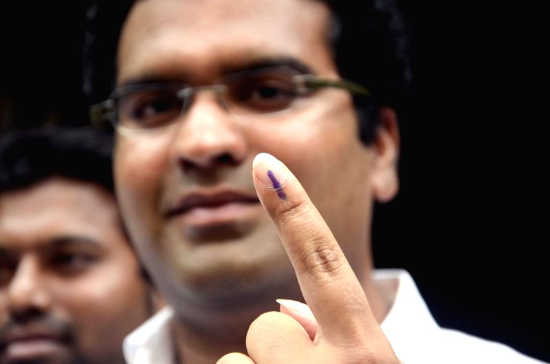 MNS candidate for 2014 Lok Sabha Election from South Central Mumbai Aditya Shirodkar shows his fore fingers marked with phosphorous ink after casting his vote at a polling booth during the sixth ...