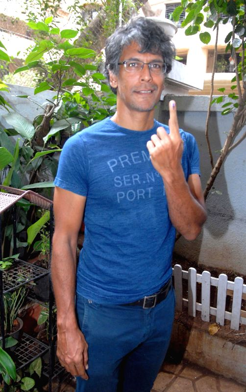 Model turned actor Milind Soman shows his fore finger marked with phosphorous ink after casting his vote during the sixth phase of 2014 Lok Sabha Polls in Mumbai on April 24, 2014.