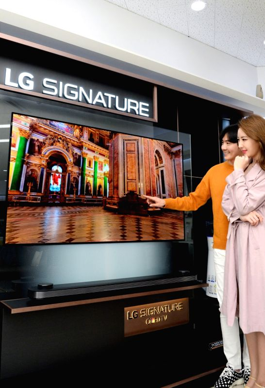 Models display an LG OLED TV at an outlet in Seoul on May 2, 2017, to promote a discount event that runs until June 29 on the occasion of the country's three terrestrial broadcasters launching ...