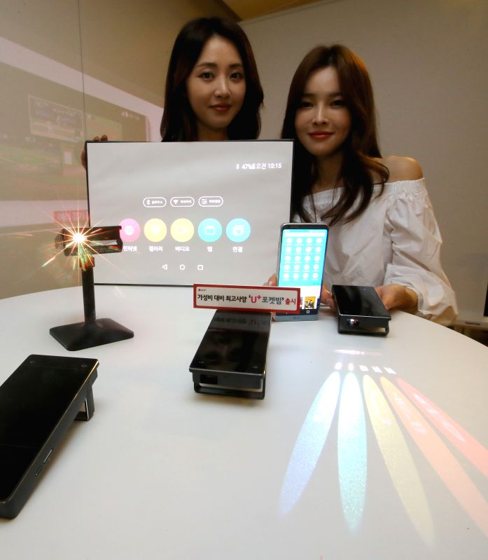 Models display LG Electronics Inc.'s LGU+ Pocket Beam projectors at an event at its headquarters in Seoul on May 11, 2017.