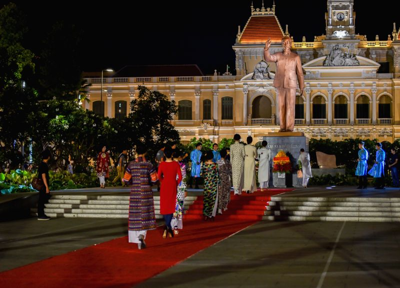 Models offer flowers to the statue of Vietnam's late leader Ho Chi Minh during the Ao Dai Show to celebrate the 126th birthday of Vietnam's late leader Ho ...