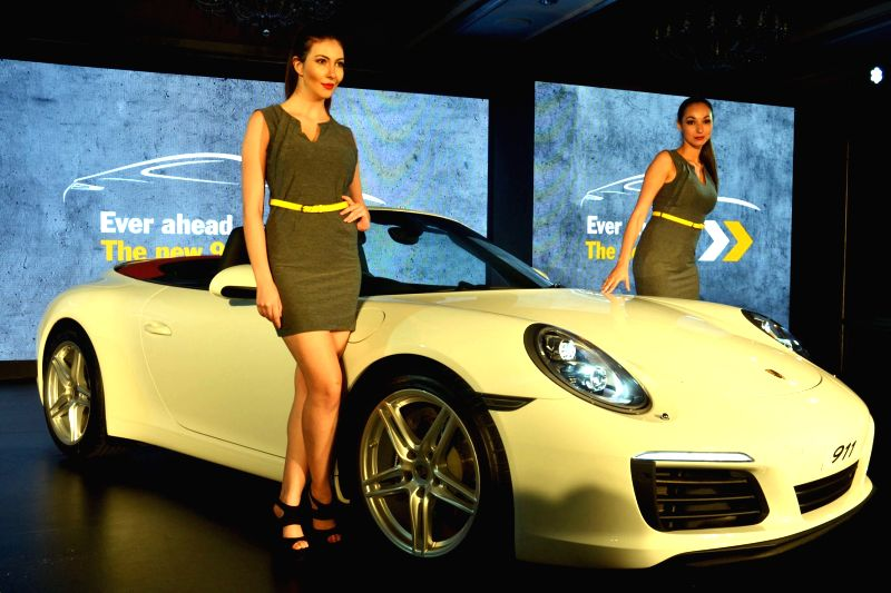 Models seen with newly launched Porsche 911 in India during a press conference, in Bengaluru on July 23, 2016.