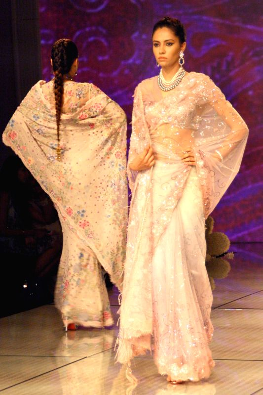 Models showcase fashion designer Tarun Tahiliani's creations during  `BMW India Bridal Fashion Week 2014` in New Delhi on Aug 7, 2014.