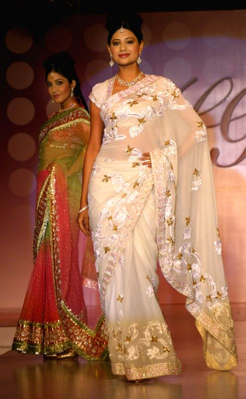 Models showcasing H G Jewelers gold jewelry collection made with enlightened swarovski elements at a fashion show, in New Delhi on Sunday.
