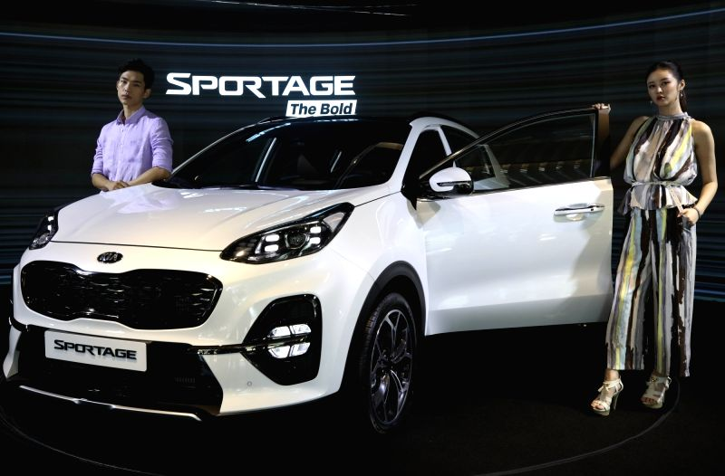 Models stand next to the Sportage The Bold, a upgraded Sportage sport-utility vehicle manufactured by Kia Motors Corp., during a publicity event in Seoul on July 24, 2018.