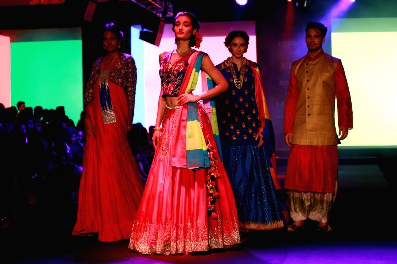 Models walk on the ramp displaying an outfit by designer Debarun Mukherjee during the Amazon India Couture Week 2015, in New Delhi on Aug 01, 2015.