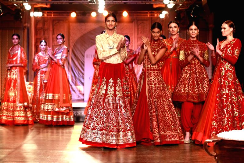 Models walk the ramp displaying an outfit by fashion designer Reynu Taandon during the India Couture Week 2016, in New Delhi on July 22, 2016.