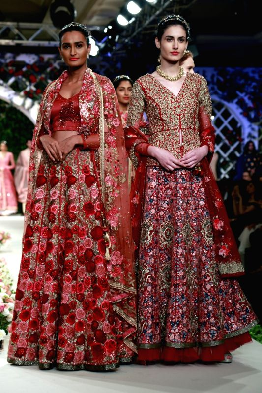 Models walk the ramp displaying an outfit by fashion designer Varun Bhal during the India Couture Week 2016, in New Delhi on July 23, 2016.