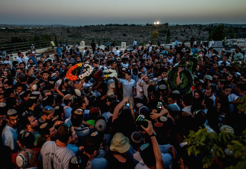 MODI'Wreaths are passed at a joint funeral for the three Israeli teens at a cemetery in Modi'in near Jerusalem, on July 1, 2014. The three Israeli teens whose bodies were - Benjamin Netanyahu