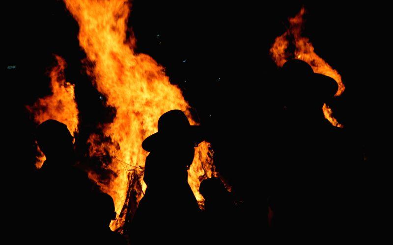 MODI'Ultra-Orthodox Jews dance around a bonfire during a Lag Baomer celebration in Modi'in Elite on May 13, 2017. Lag Baomer marks the hillula (celebration, ...