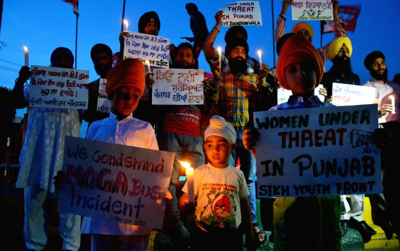 People participate in a candle light vigil to condole the death of of a 13-year-old girl who jumped out of a moving bus to escape molestation on 30th April 2015 near Moga town of Punjab; in ...