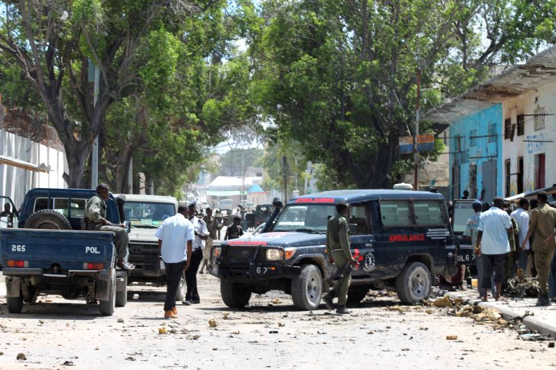 Police and emergency service are seen at the scene of a suicide car explosion in Mogadishu, Somalia, April 21, 2015. Ten people were killed in a car explosion ...