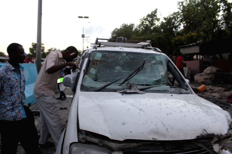 MOGADISHU, May 25, 2017 - People check the remains of a car at the site of an explosion in Mogadishu, Somalia, May 24, 2017. At least five people were killed and an unknown number injured in a ...