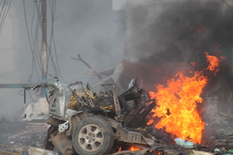 A car is on fire outside the hotel which was attacked in Mogadishu, capital of Somalia, Nov. 1, 2015. At least 12 people were killed Sunday as Al-Shabaab ...